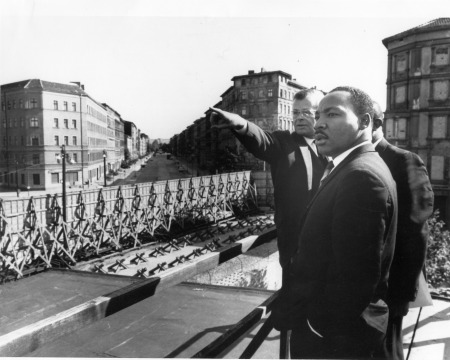 Dr. King is standing at the Soviet Sector border of the Wall, while the director of the Berlin Information Center is indicating points of interest. Reference 306-BN-466-4880