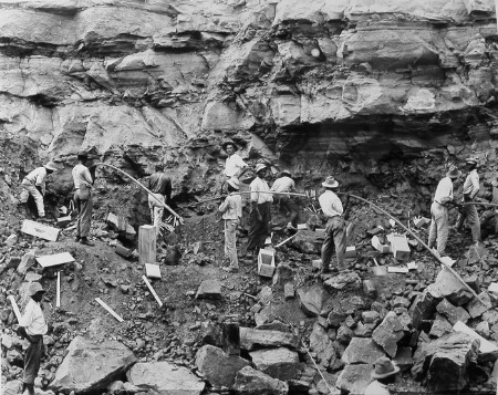 """Working with dynamite was one of the most dangerous jobs in the Canal Zone. Deaths and severe injuries to these laborers were not uncommon. In this February 1912 photograph several """"powder men"""" are shown loading shot holes with dynamite to blast a slide of rock in the west bank of the Culebra Cut.  (National Archives Local Identifier 185-G-154)"""