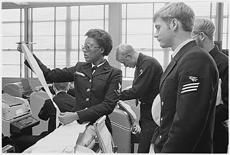 """Service School Command, San Diego, California...Radioman third class Denita G. Harvey, left, of Los Angeles, California, checks a student's typing performance for accuracy following a timed drill. Miss Harvey is an instructor at the Navy Radioman """"A"""" school. [African-American woman working.] (NAID 558536)"""