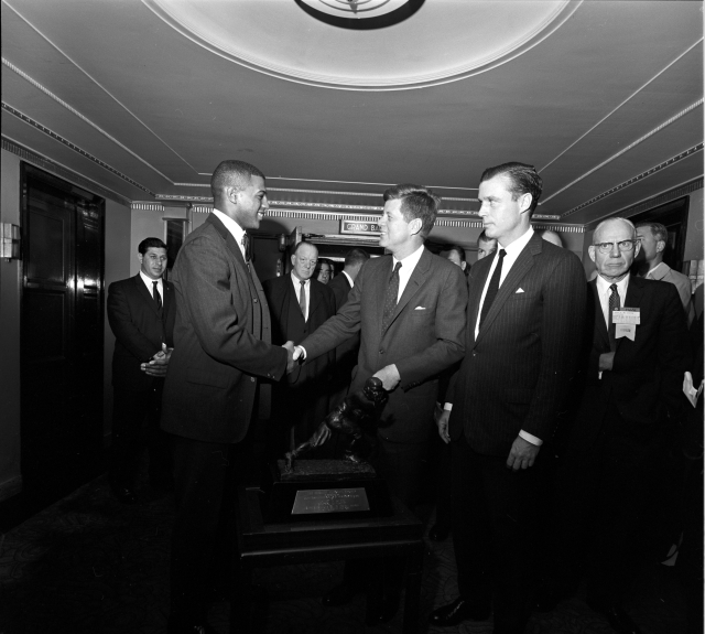 ST-274-2-61 5 December 1961 President Kennedy meets Heisman Trophy winner, Ernest Davis at the Waldorf Astoria Hotel in New York City. The President was attending the National Foundation (Football) Hall of Fame Dinner. Others unidentified. Photograph by Cecil Stoughton, in the JOhn F. Kennedy Presidential Library and Museum, Boston